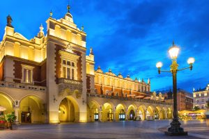 Illuminated palace on old town square at night Krakow, Poland. Jewish Heritage in Central Europe